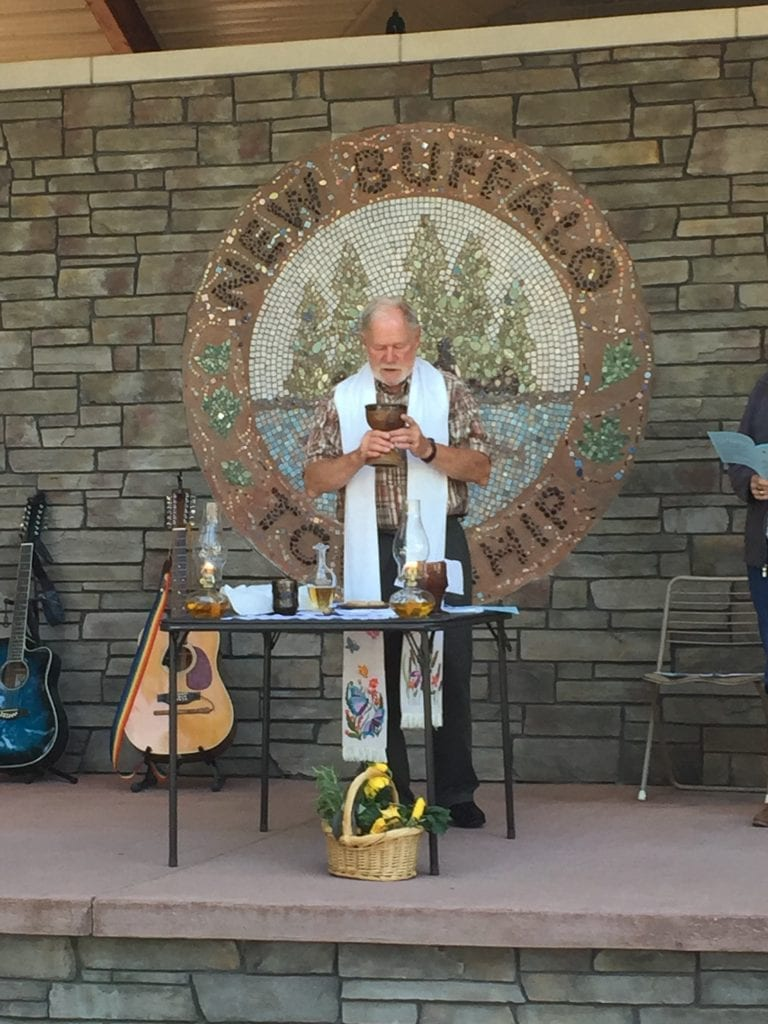 Father David Brower offers the cup of wine at the 2019 worship service and picnic
